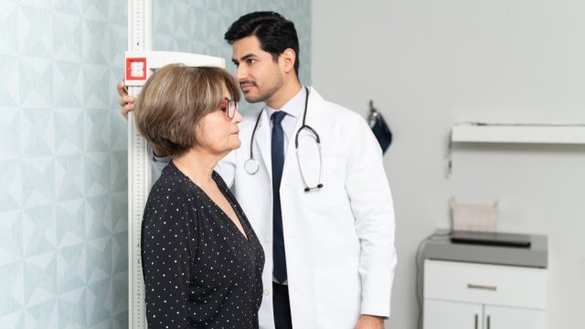 male physician measuring height of senior woman in hospital