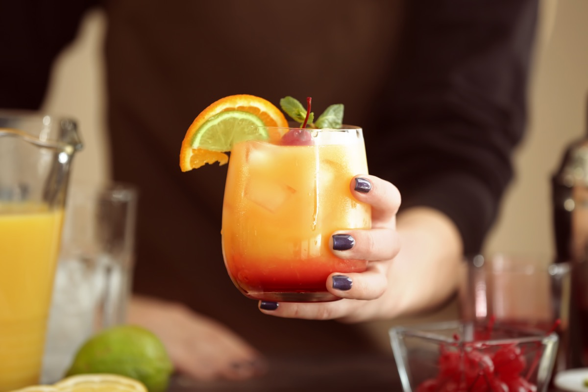 a woman holding glass of tequila sunrise cocktail
