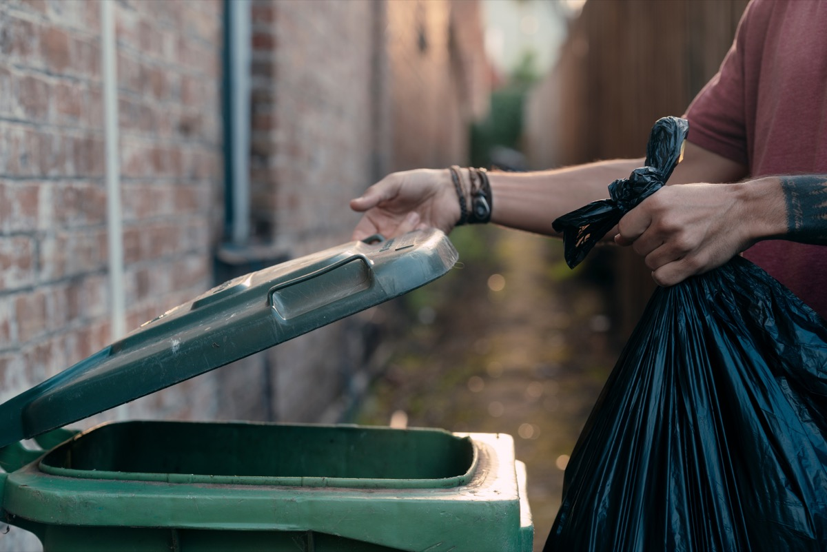 person throwing trash in outdoor bin