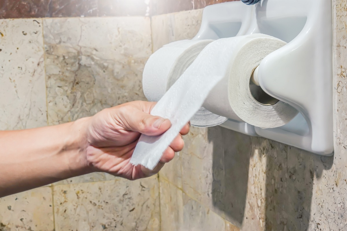 hand reaching for toilet paper roll