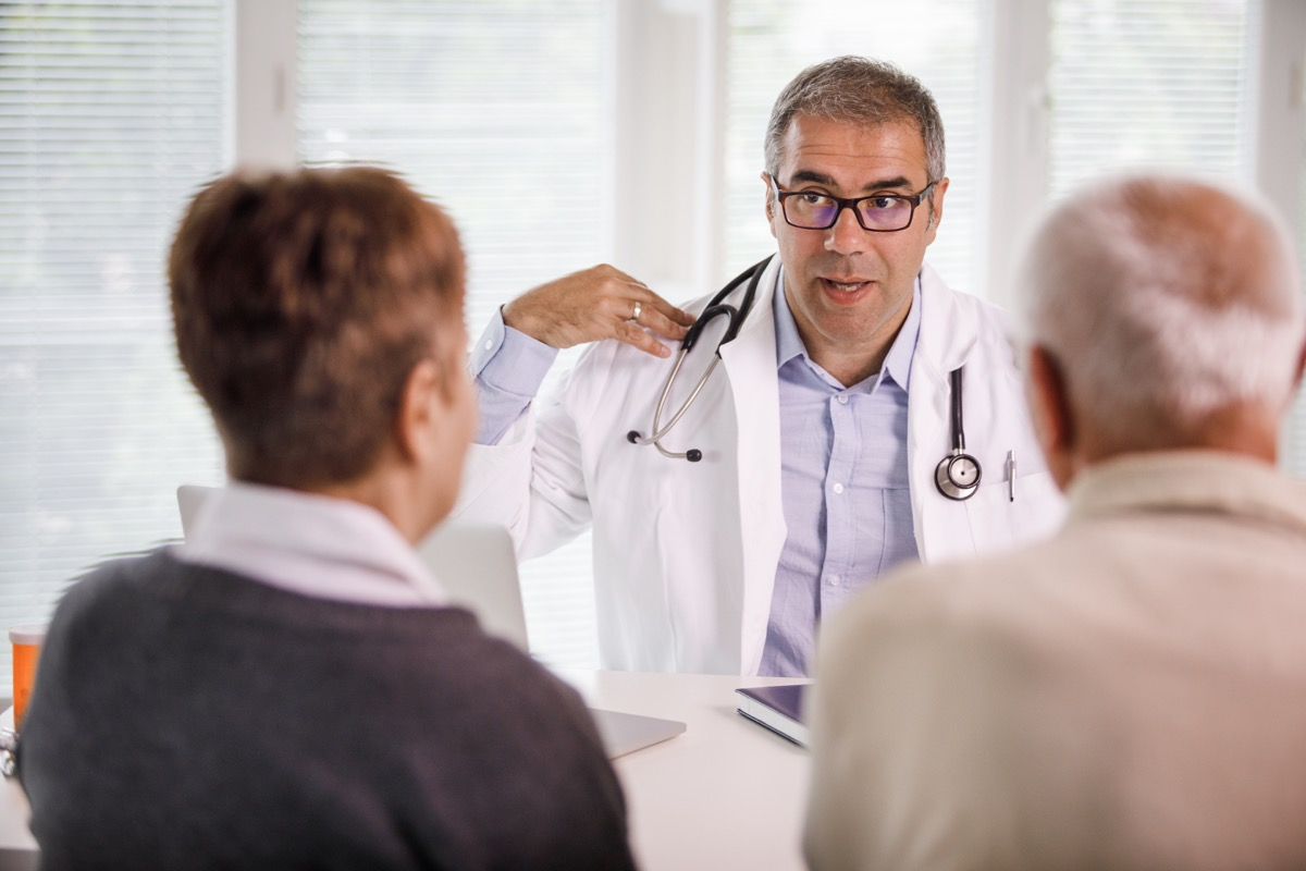 Selective focus of a mid-adult positive doctor explaining physical therapy exercises during medical consultation to an elderly couple sitting in front of him.