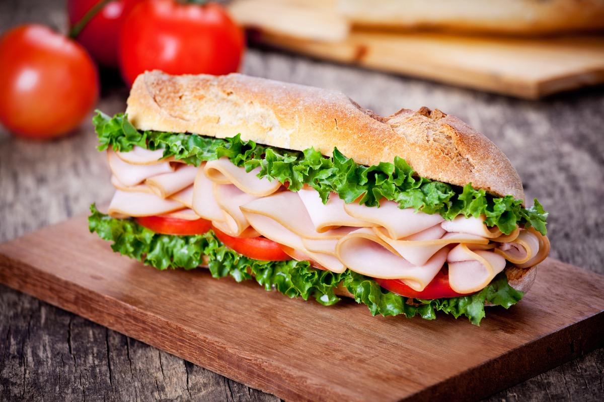 turkey sandwich, wooden board, lettuce, tomato