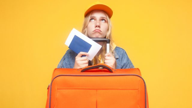 unhappy tourist with luggage looking sad on a yellow isolated background