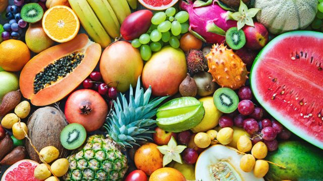Assortment of colorful ripe tropical fruits, including watermelon