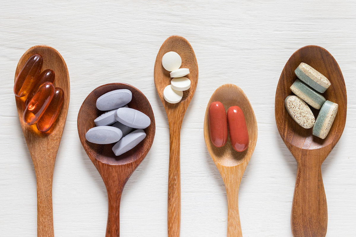 Variety of vitamin pills in wooden spoon on white background