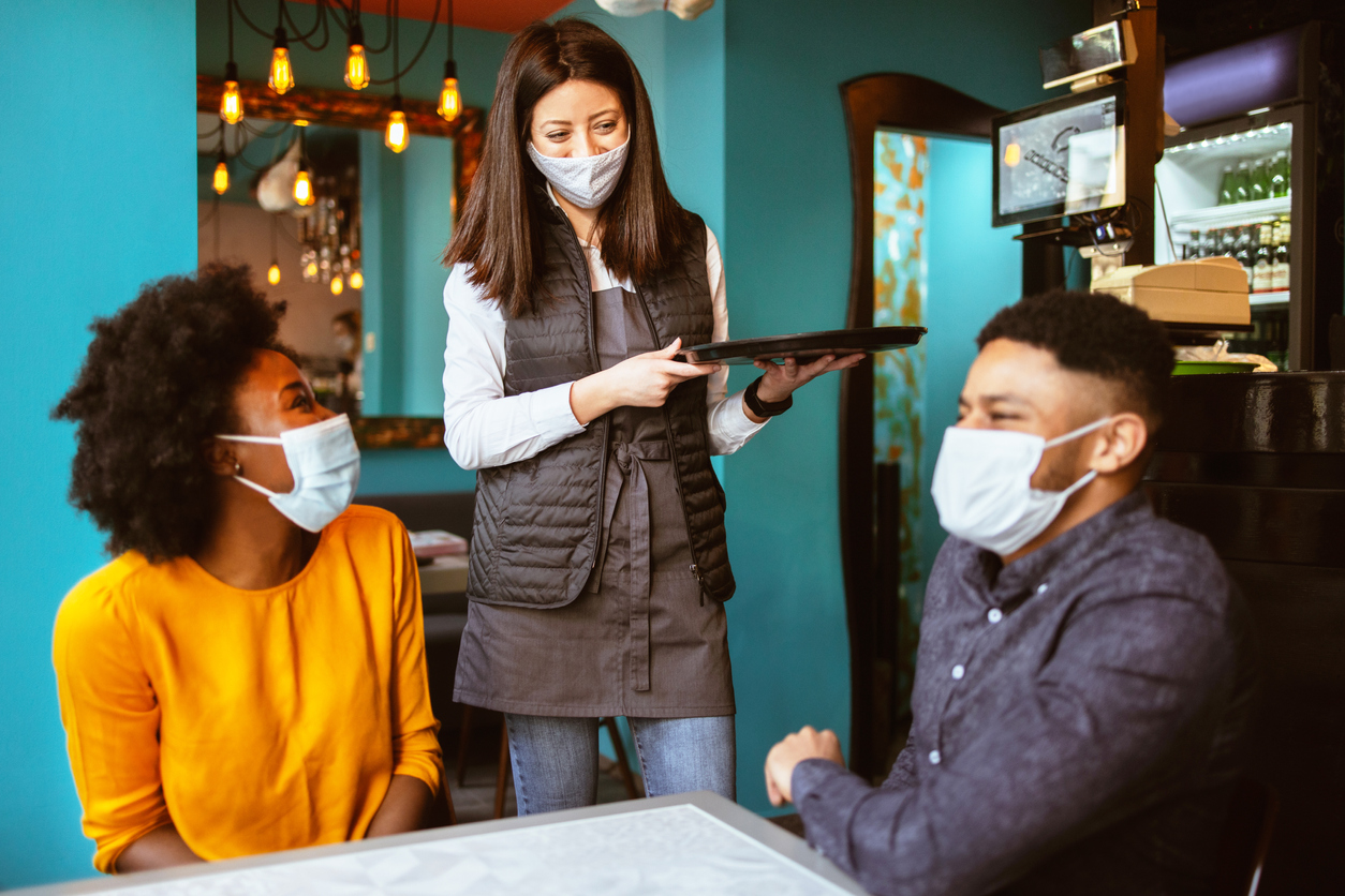 A young server speaks to a couple sitting at a table at a restaurant while all wear face masks