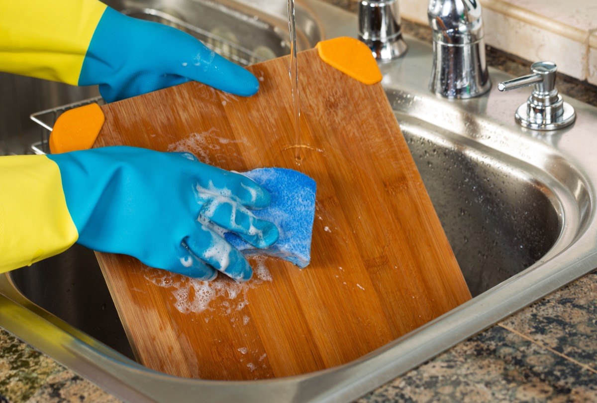 person wearing rubber gloves washing cutting board with soap
