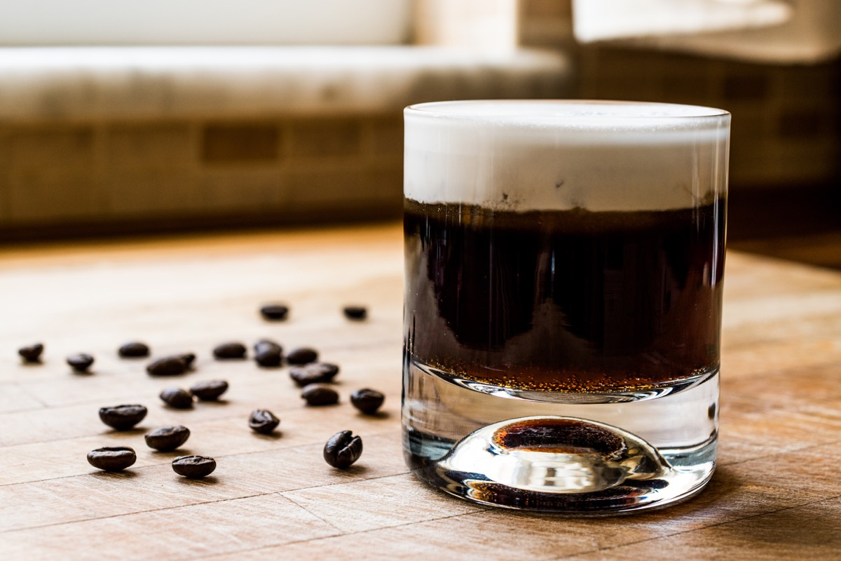 white russian cocktail in glass, on table, alongside coffee beans