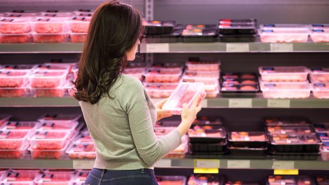 woman buying meat at supermarket