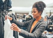 woman with curly hair in orange turtleneck and gray sweater clothing shopping