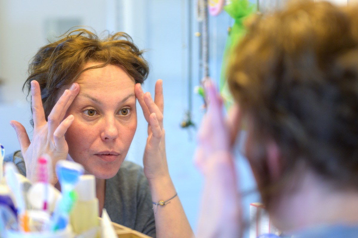 woman checking out her face in a mirror during her morning with a view to her reflection in the mirror