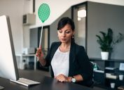 woman holding green flyswatter at desk
