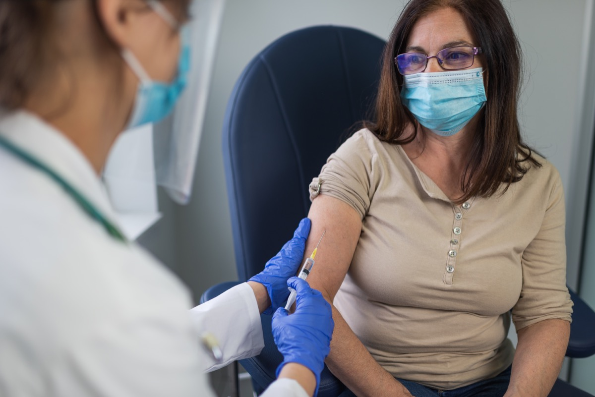 Close up of a mature woman taking a vaccine in her doctors office.