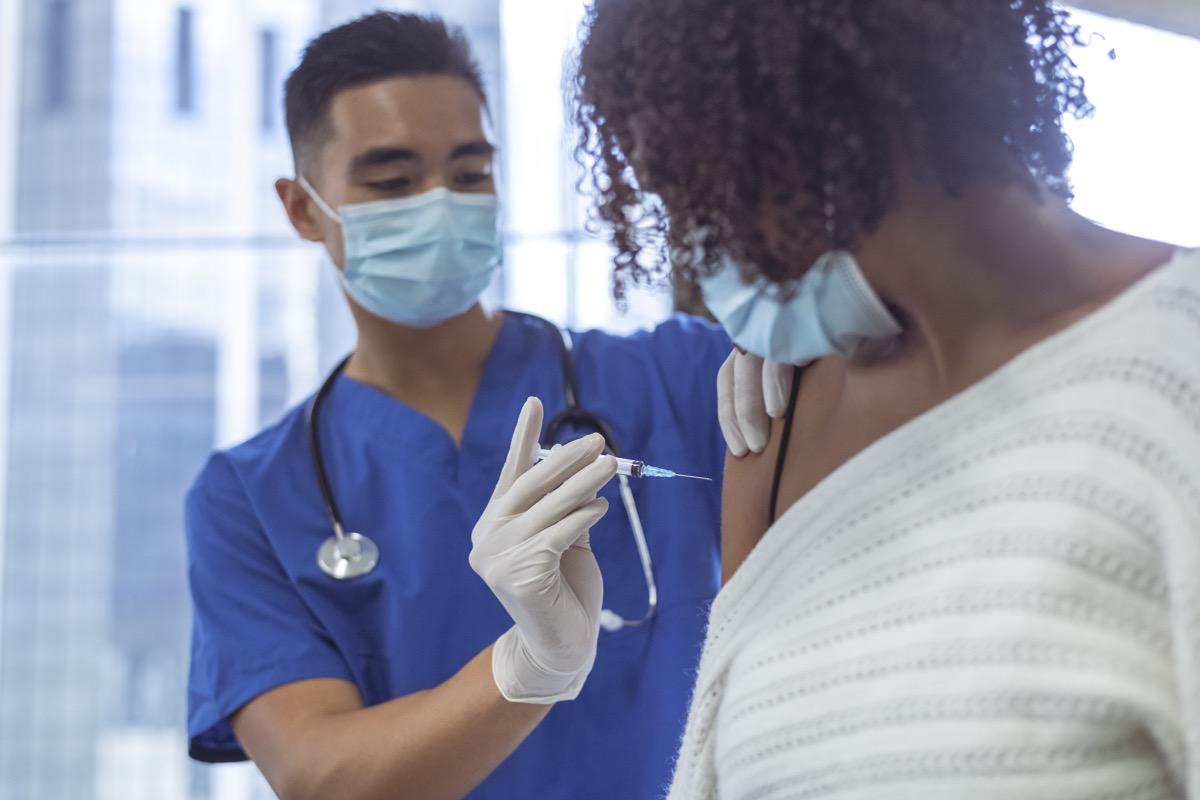 Shot of a male nurse wearing blue medical scrubs, giving vaccine