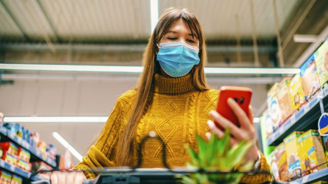 A young woman wearing a face mask looks at her phone while grocery shopping