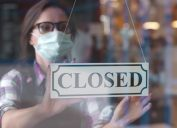 woman in face mask hanging closed sign in restaurant window