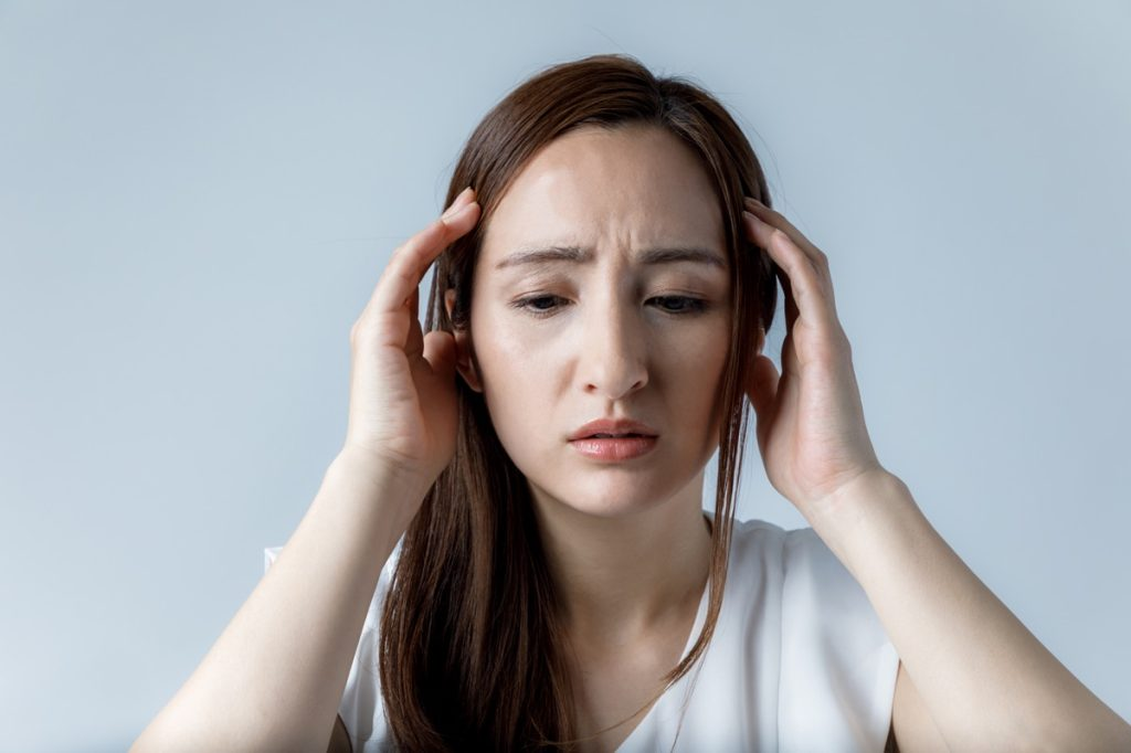 woman touching her head, looking nervous