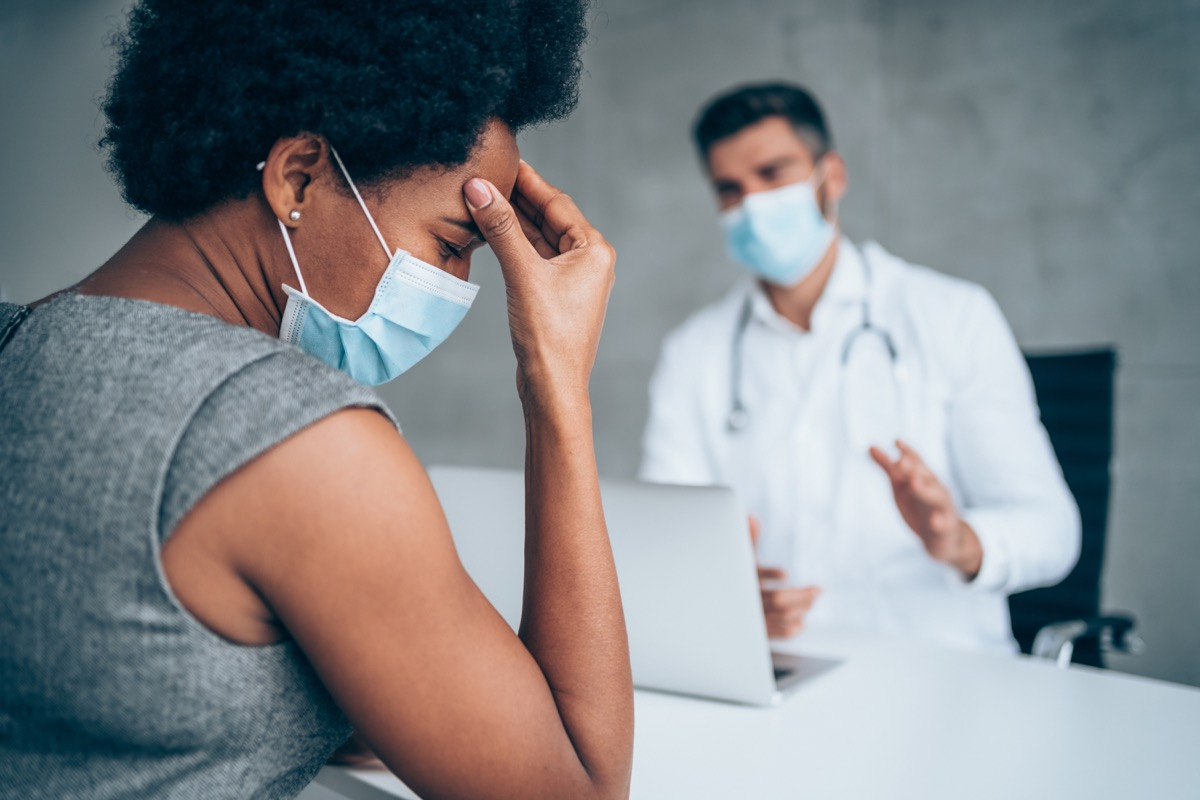woman sitting opposite the doctor in his office and holding her head with hand.