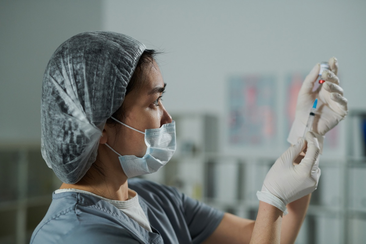 protective workwear preparing injection for patient in medical office of contemporary clinics