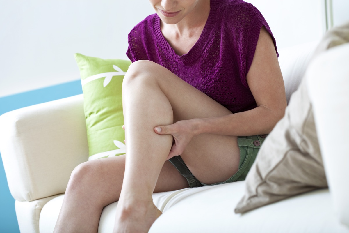 woman touching her leg, calf pain, leg pain, sitting on couch