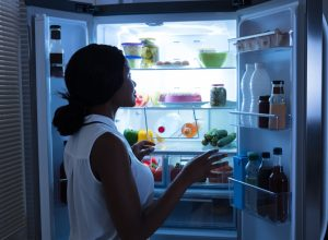 young woman opening the fridge at night in dark kitchen