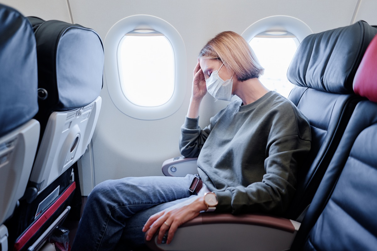 woman sitting on a plane with facemask