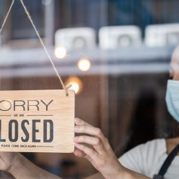 A woman wearing a mask putting up a closed sign on the door of a restauratnt