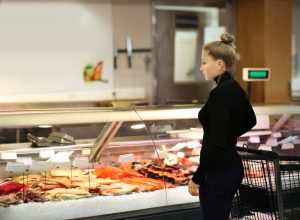 A woman shopping in the seafood section of the grocery store