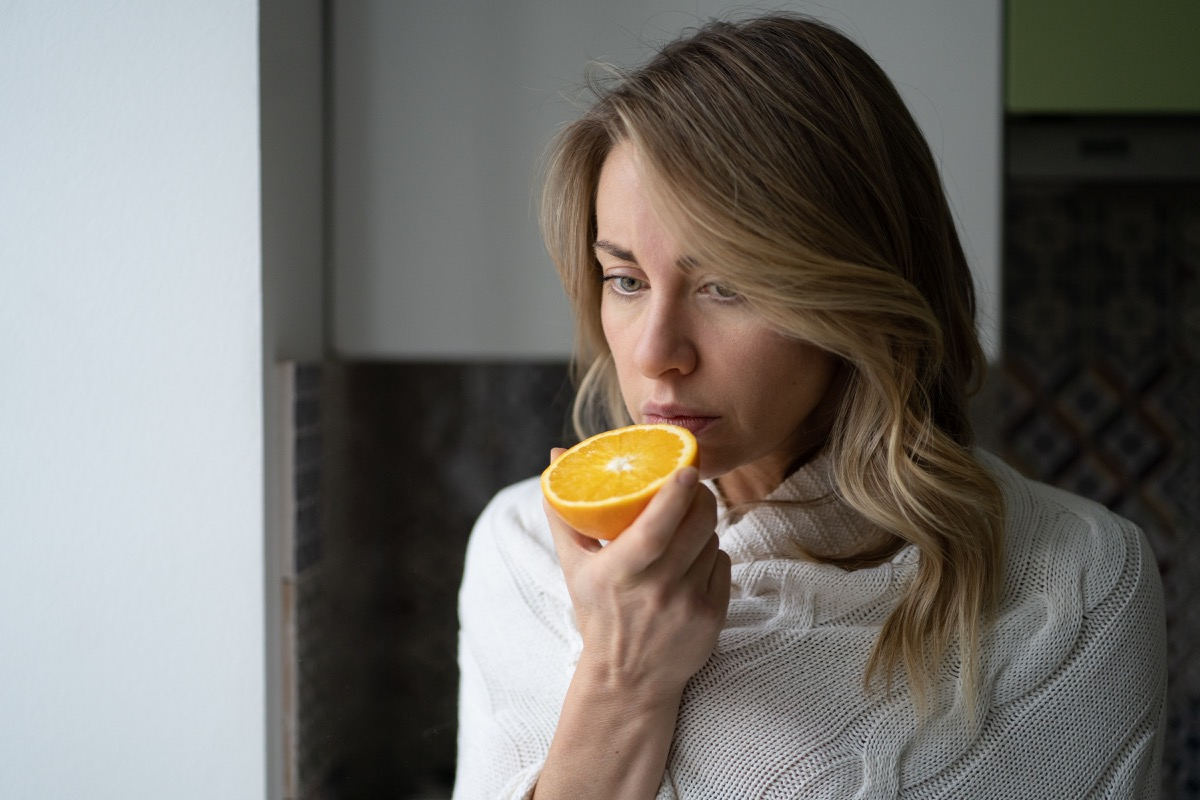 woman trying to smell half an orange