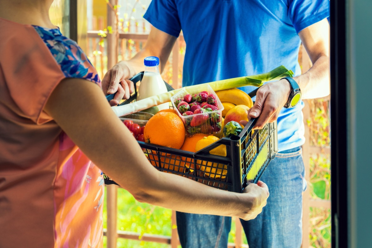 woman taking crate of dairy and produce from delivery person