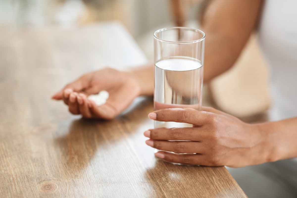 woman takes medicines with glass of water at home, cropped image, closeup