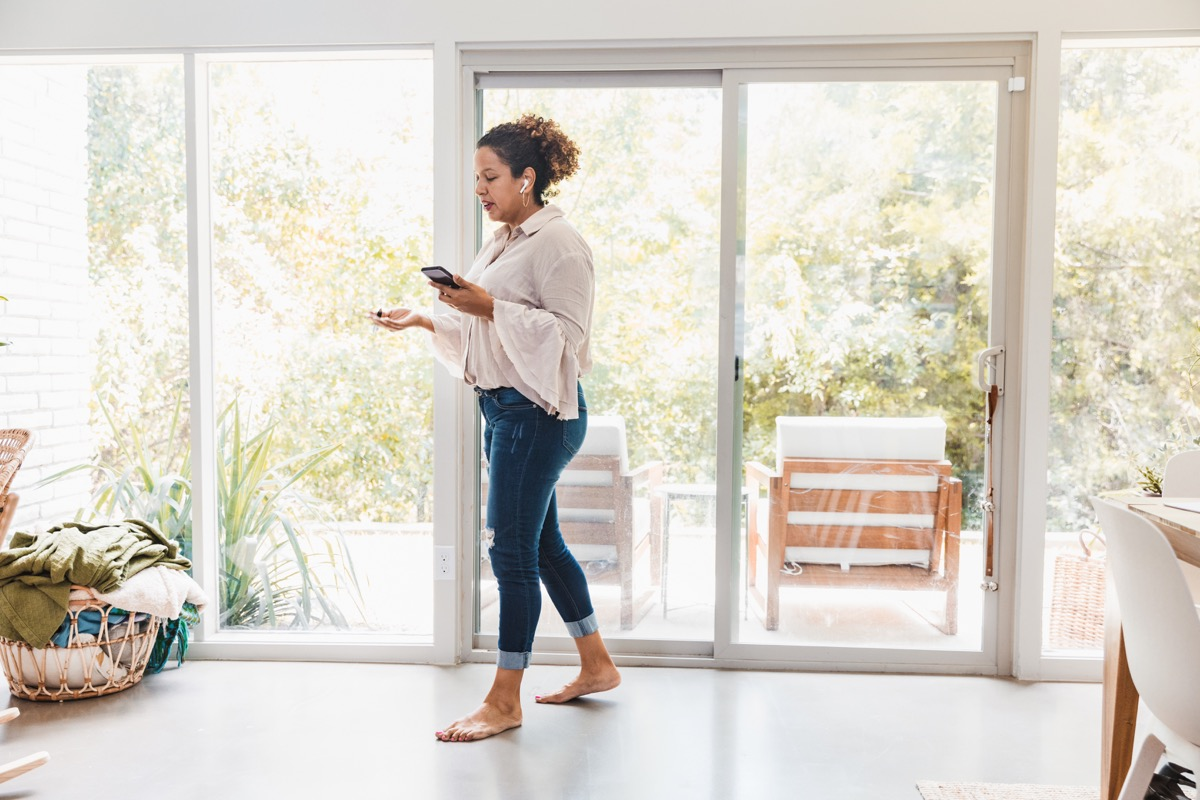 Wearing casual clothes and walking barefoot at home, the mid adult business woman joins colleagues for a video conference.