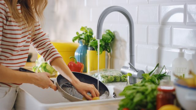 A woman washing dishes in the kitchen sink