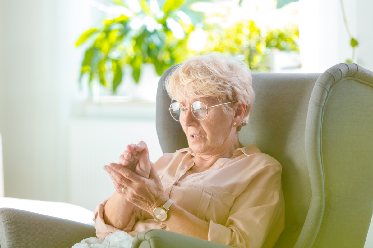 Elderly woman suffering from pain in hand at home, she is sitting in armchair in her room