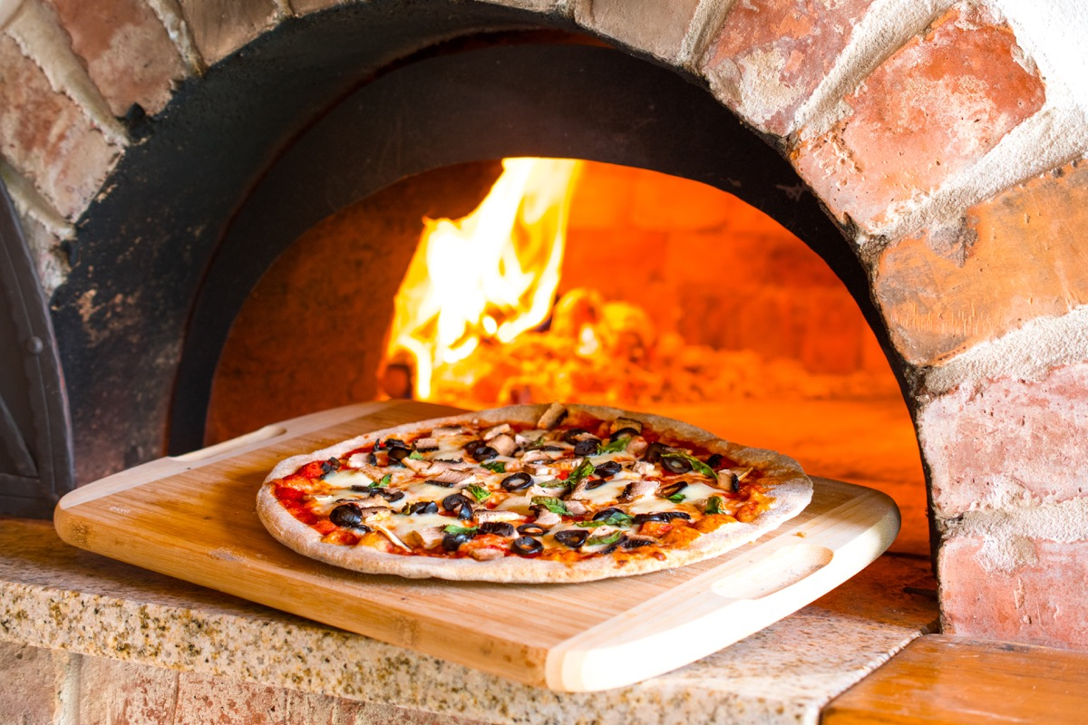 a pizza outside a brick oven, pizza oven