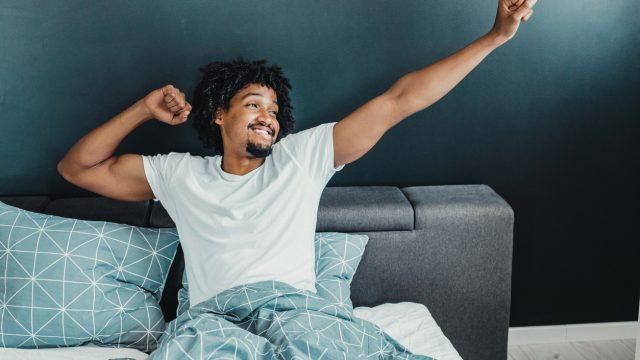 A young man waking up in the morning and stretching his arms whlie smiling