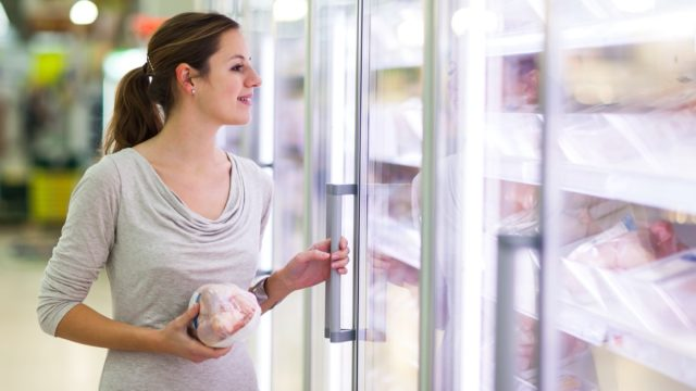 young woman buying meat at supermarket while holding fridge door open