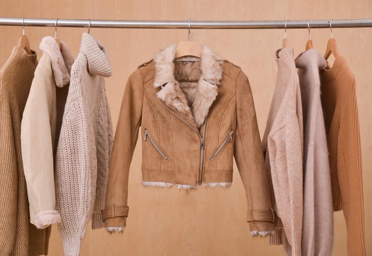 Fur trim suede jacket on rack