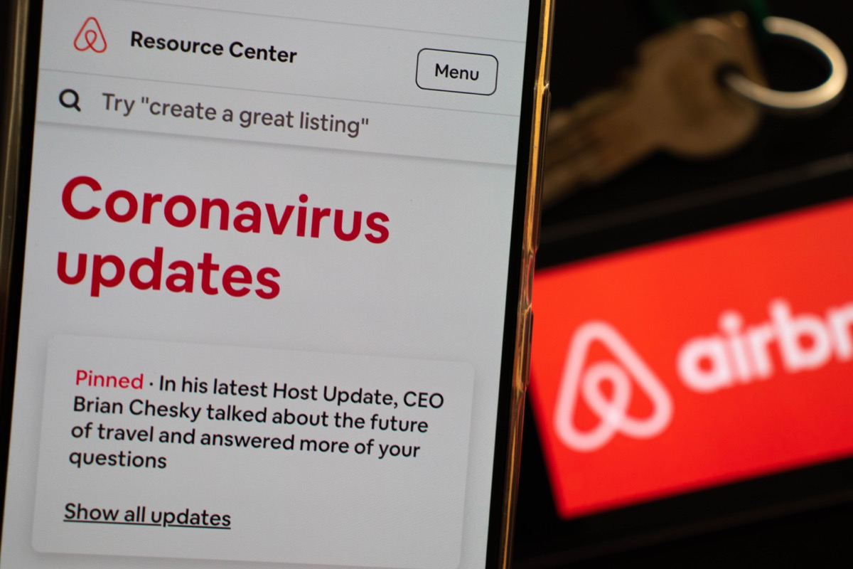Milan, Italy - 05 16 2020: An Airbnb host is checking last updates on Airbnb app regarding covid-19 coronavirus and its impact on tourism and hospitality policies. Vacation business is in a crisis