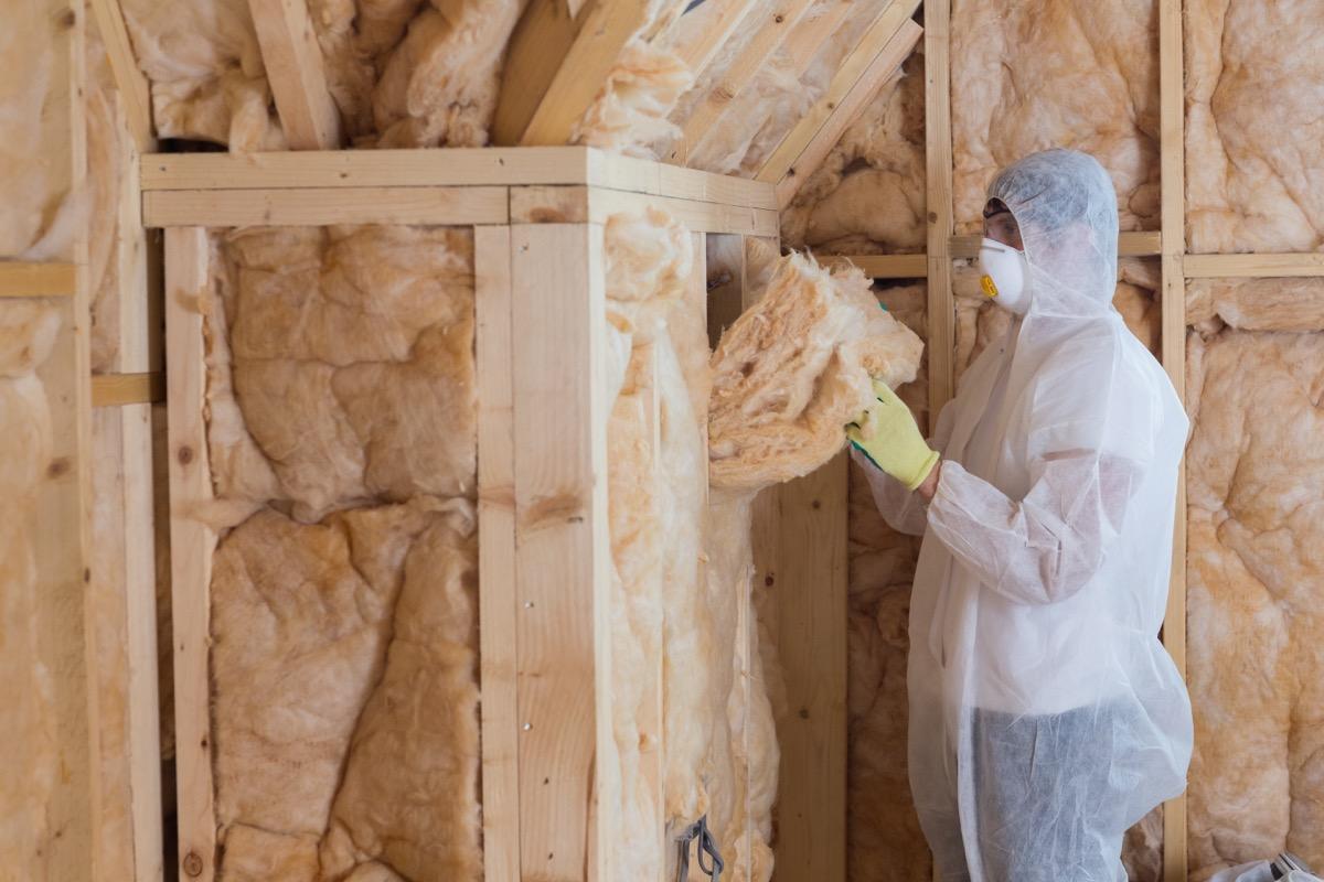 person in tyvek suit installing attic insulation