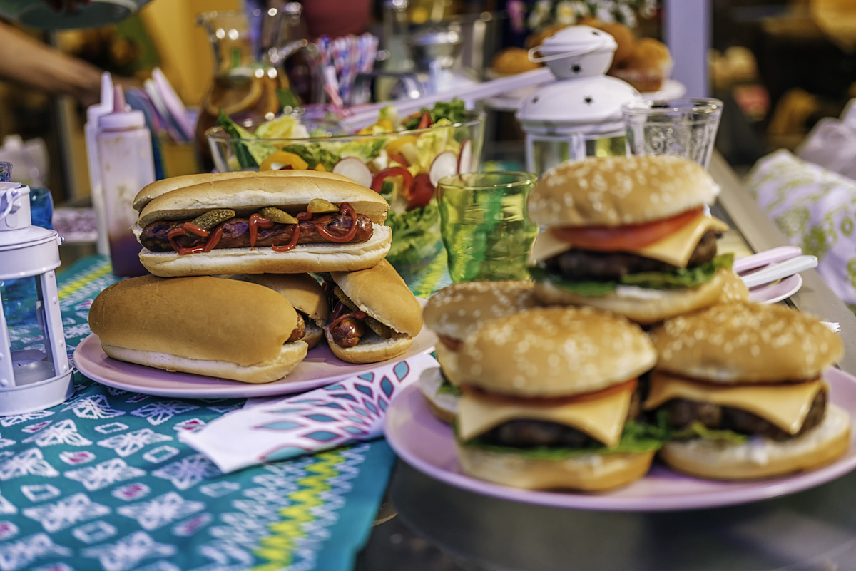 Preparing homemade burgers with tomatoes, onions and salad