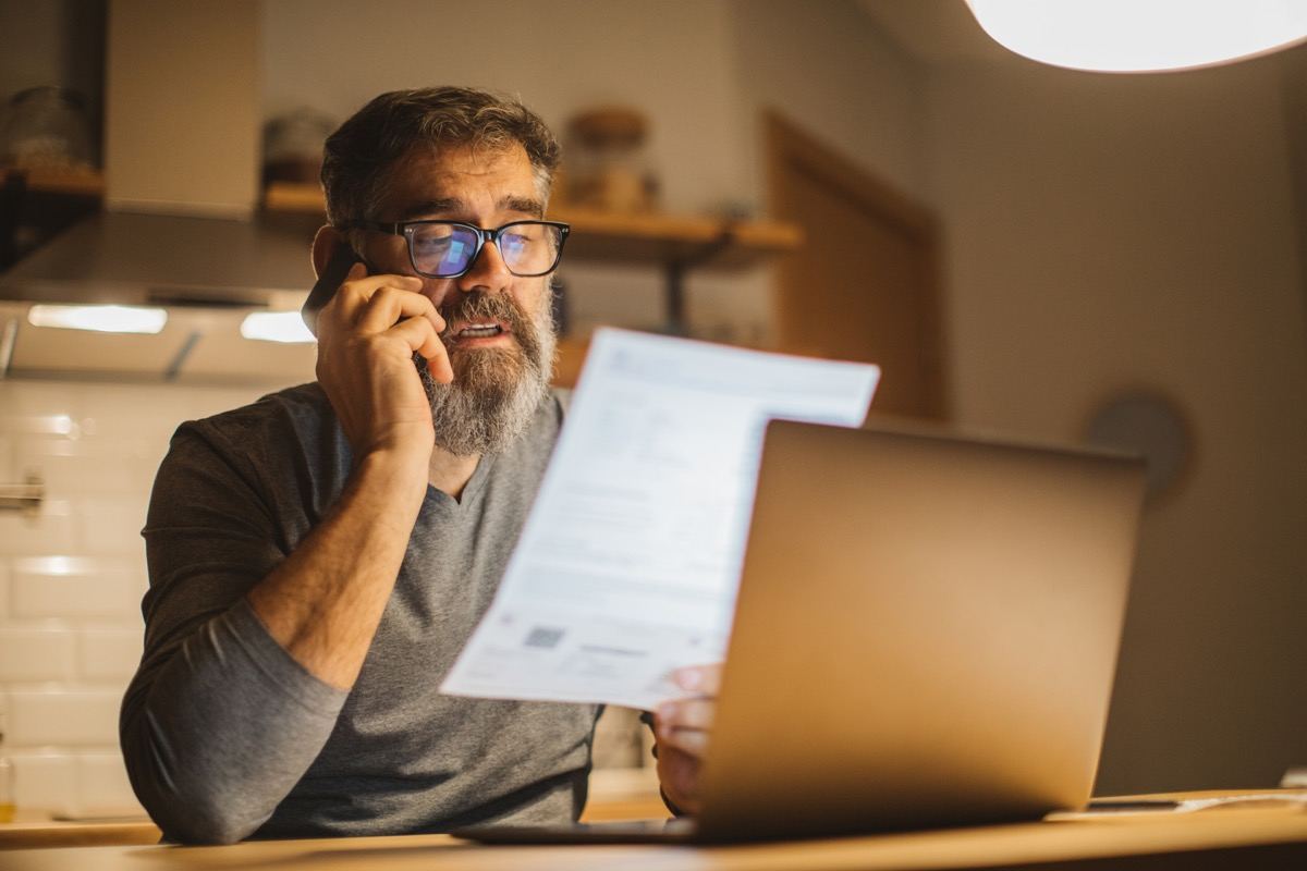 Mature men at home during pandemic isolation reading something on laptop