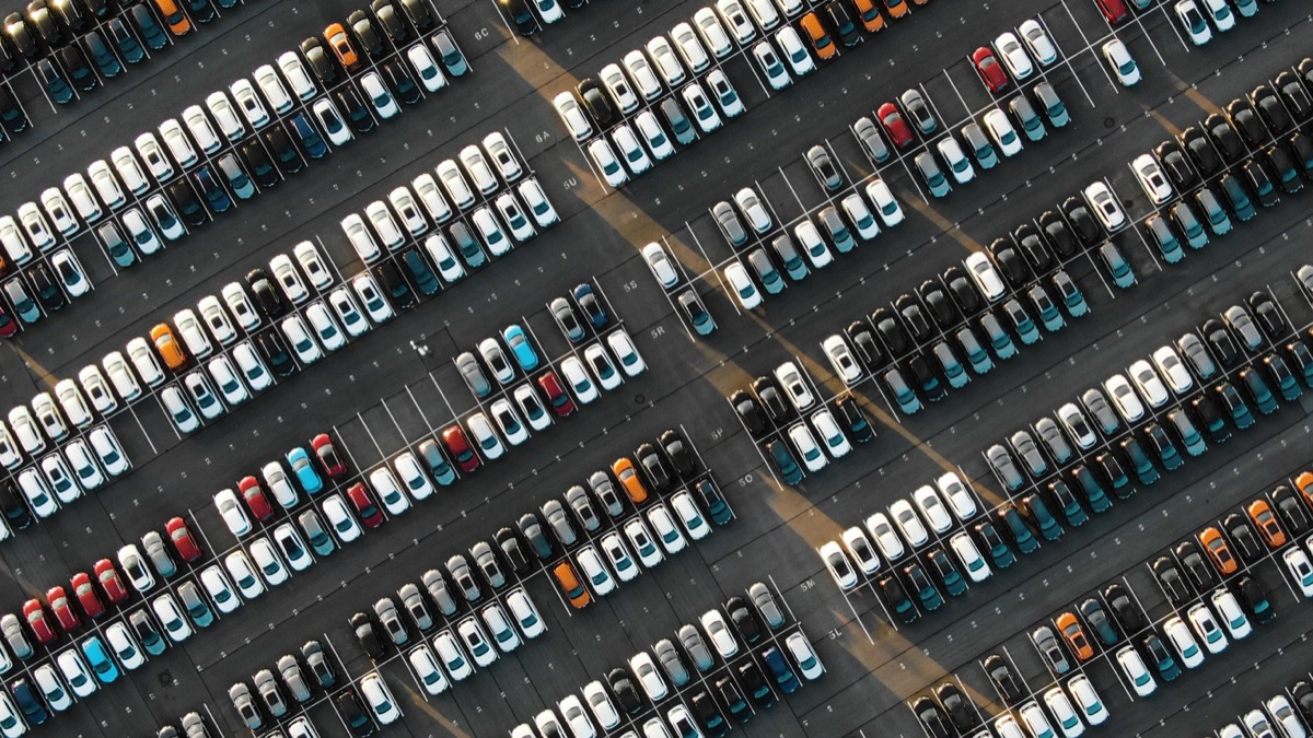 dozens of cars parked, for sale in a parking lot