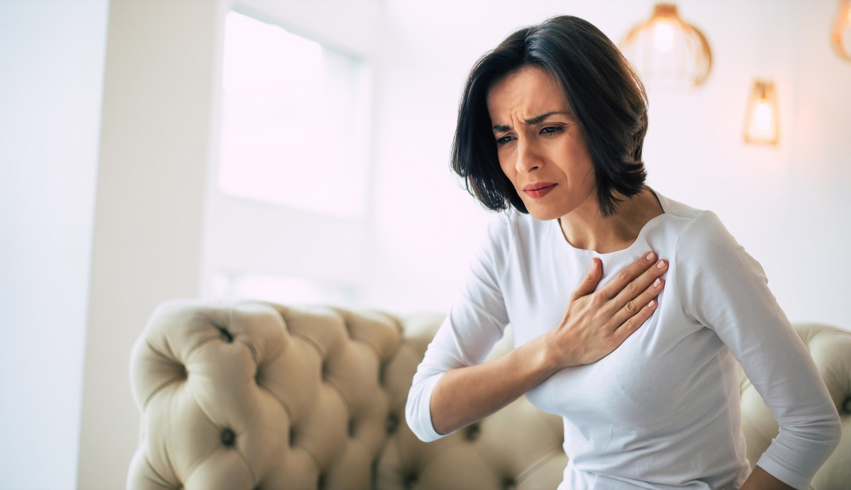 woman having chest pain, hand over her heart