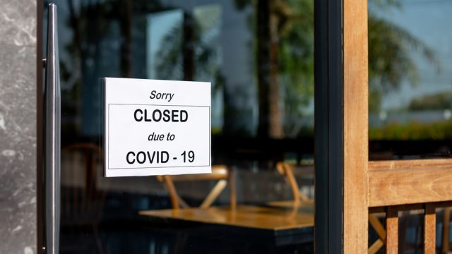 A closed sign hanging on the front of a business due to COVID-19 lockdowns