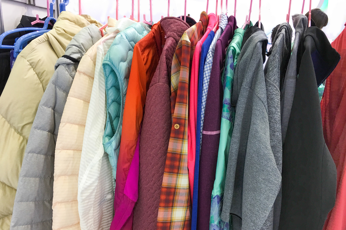 Colorful coats, jackets, and hoodies hanging in closet