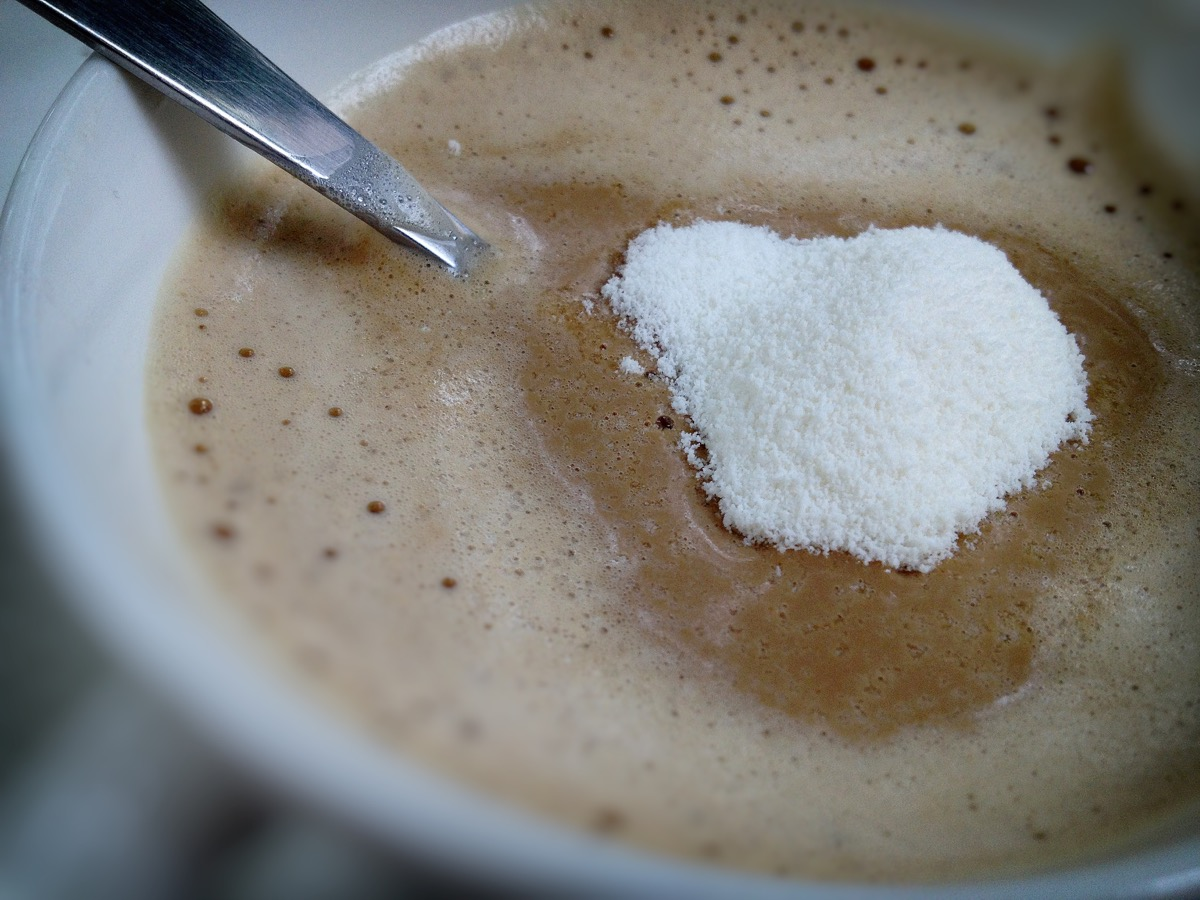 spoon with non-dairy or powdered coffee creamer being stirred into cup