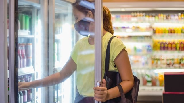 woman with face mask opening freezer door, taking some cold drinks in convenience store during Covid 19 pandemic