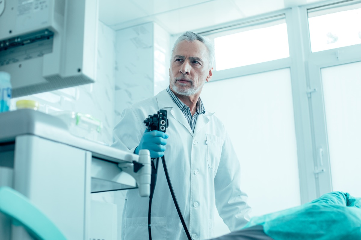 Calm mature medical worker standing with an endoscope and looking at the screen stock photo