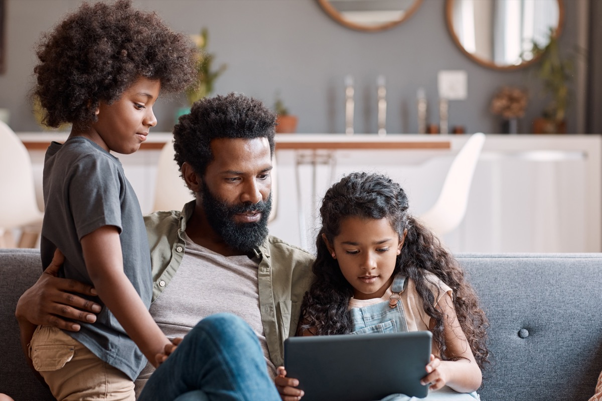 Shot of two adorable young siblings using a digital tablet while bonding and relaxing with their father at home